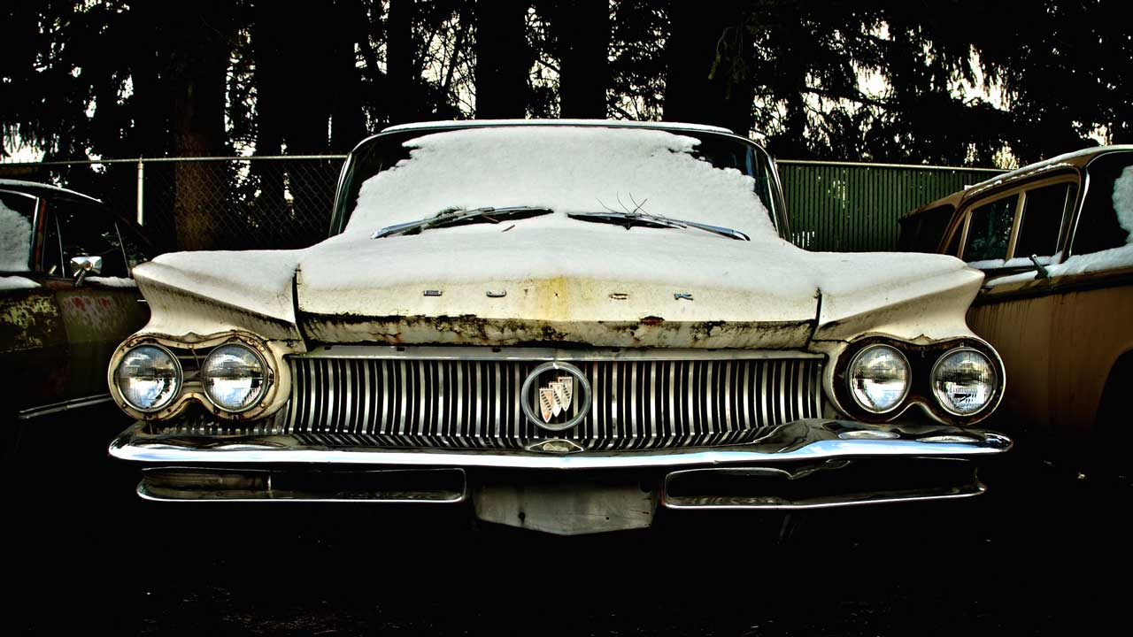 old rusty buick sitting outside